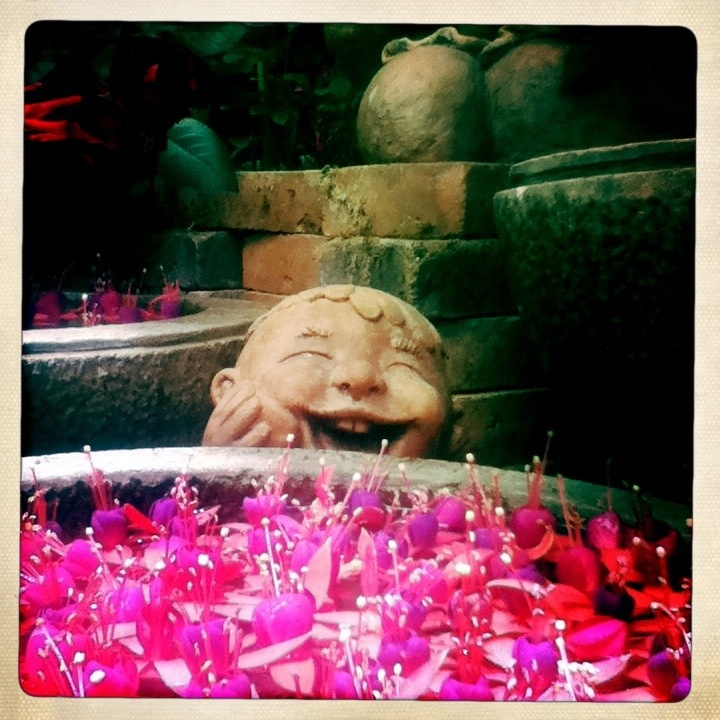 Laughing statue in Thailand with pink flowers Hipstamatic
